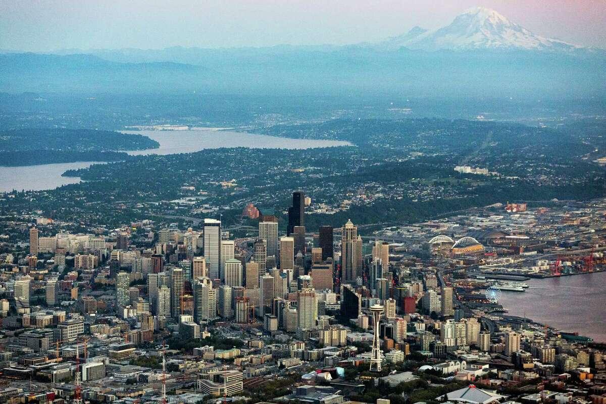 Mount Rainier appears in the twilight behind the Seattle skyline, Lake Washington (left) and Elliott Bay (right).