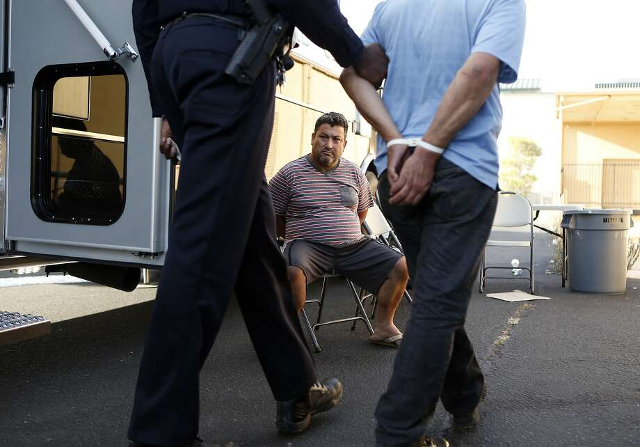 Gabriel Moreno watches as Richmond police arrest another prostitution suspect, Rogelio Gutierrez, during a sting. Photo: Scott Strazzante, The Chronicle