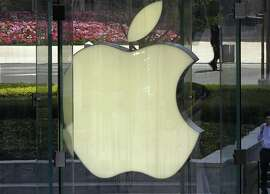 In this April 2, 2013, file photo, a man smokes near the logo of Apple in Shanghai. Apple is expected to unveil its latest version of the iPhone on Tuesday, Sept. 10, 2013. (AP Photo/Eugene Hoshiko, File)