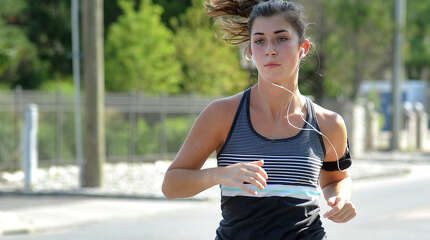 Emily Marren, 21, of Fairfield, a recent graduate of Oberlin College, wears headphones while she runs Friday, Sept. 5, 2014, near her home in Fairfield, Conn.