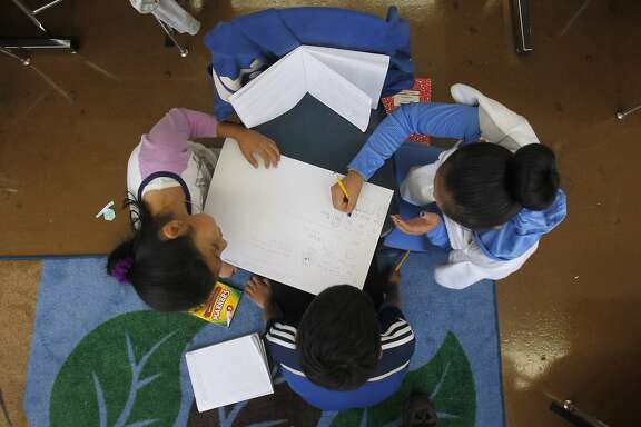 Patricia Martinez Tejeda (left), Kismot Rakkat (center) and Phung Nguyen team up to solve a math problem in Mai-tien Nguyen's 4th grade class at Redding Elementary School in San Francisco, Calif. on Thursday, Sept. 4, 2014. Schools throughout the district are fully implementing the Common Core curriculum this year.