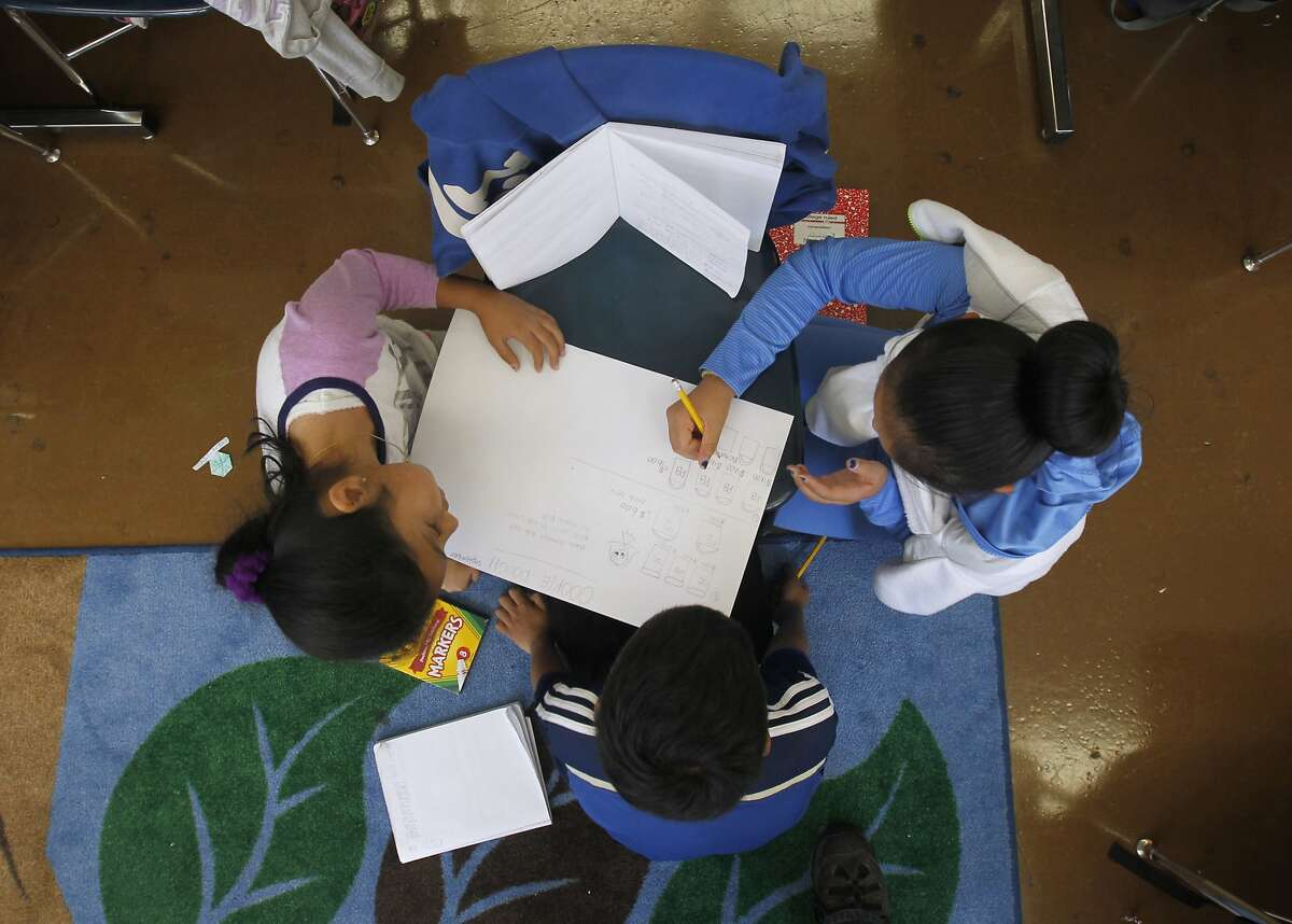 Patricia Martinez Tejeda (left), Kismot Rakkat (center) and Phung Nguyen team up to solve a math problem in Mai-tien Nguyen's 4th grade class at Redding Elementary School in San Francisco, Calif. on Thursday, Sept. 4, 2014.