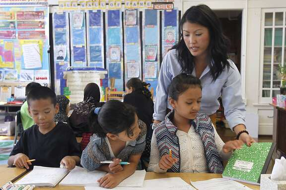 Teacher Mai-tien Nguyen helps 4th graders Lauren Salyphanh (left), Malak Hadwan (center) and Sneha Limbu with a math problem at Redding Elementary School in San Francisco, Calif. on Thursday, Sept. 4, 2014. Schools throughout the district are fully implementing the Common Core curriculum this year.