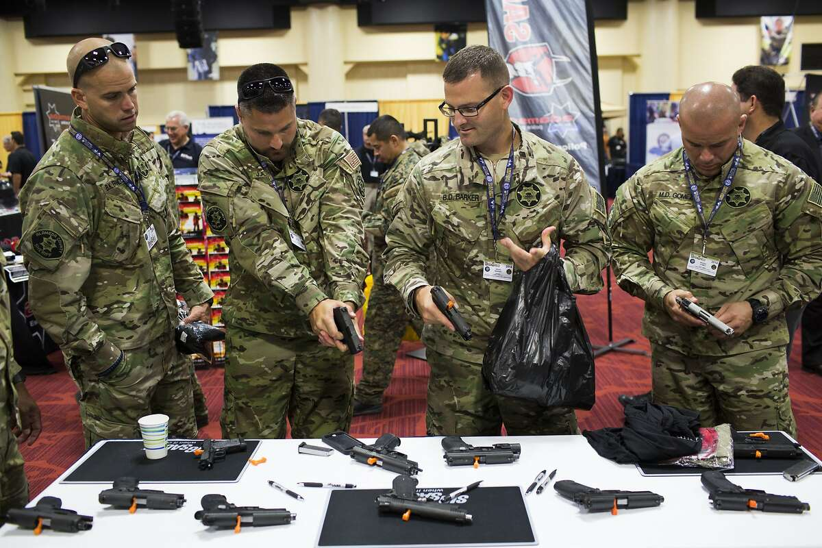 From left to right, Bryan Francis, Justin Miguel, Brian Barker and Moises Gomez of Alameda County Sheriff's Department test Sig Sauer handguns at Urban Shield, a five-day event showcasing the latest in law enforcement equipment, at the Oakland Marriott City Center in Oakland, Calif. on September 5, 2014.