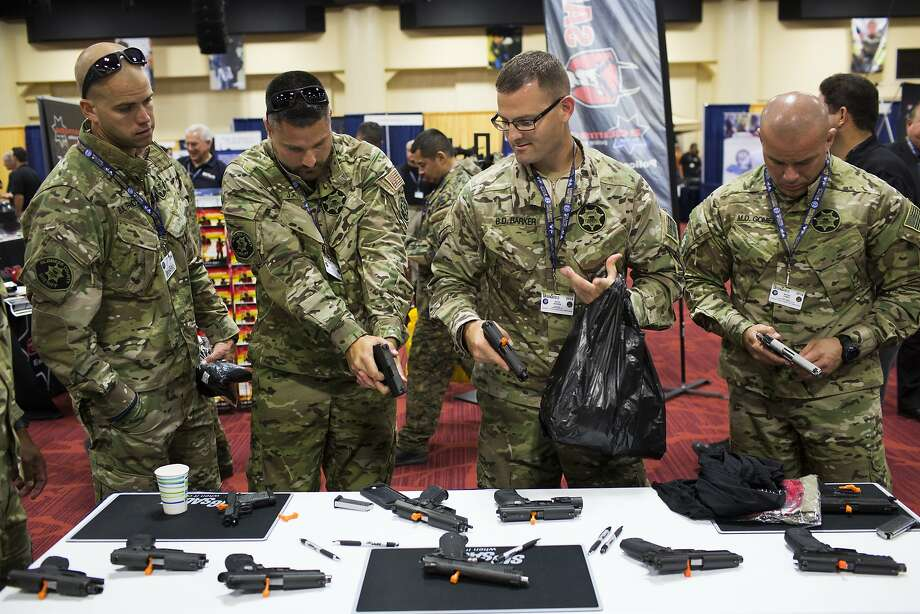 Bryan Francis (left), Justin Miguel, Brian Barker and Moises Gomez of the Alameda County Sheriff's Office test Sig Sauer handguns at the Urban Shield trade show in Oakland. Photo: Tim Hussin, Special To The Chronicle