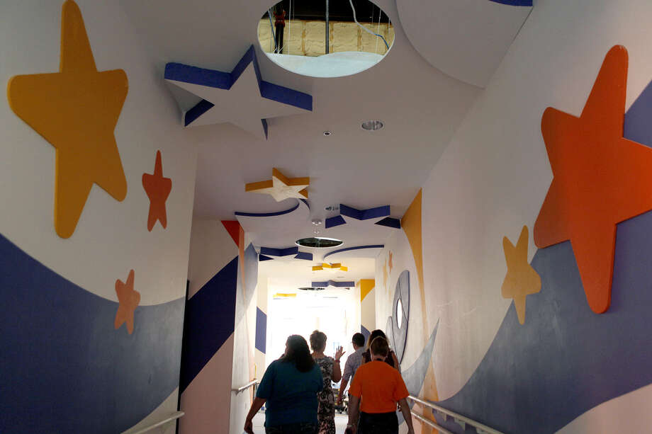People tour the space-themed hallway of the Children's Rehabilitation Institute of TeletónUSA. The clinic will serve children with neuromusculoskeletal disorders, and is set to open at the end of October. Photo: Photos By Cynthia Esparza / For The Express-News / For the San Antonio Express-News