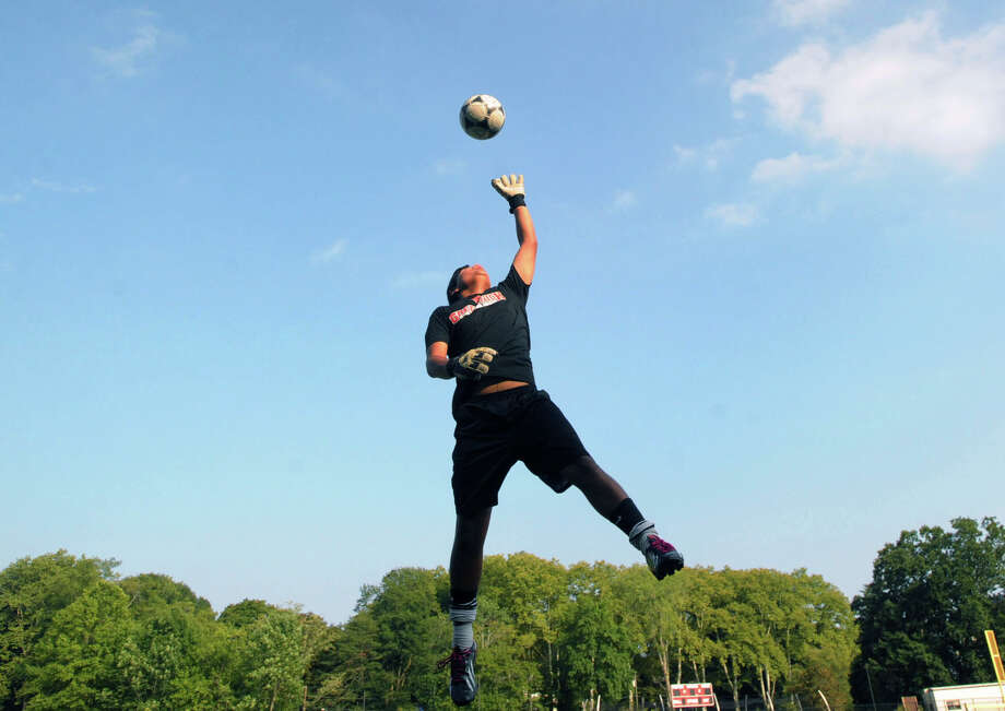 Greenwich High School boys varsity soccer player, Jose Romero, a goalie, deflects the ball during practice at the school in Greenwich, Friday afternoon, Sept. 5, 2014. Photo: Bob Luckey / Greenwich Time