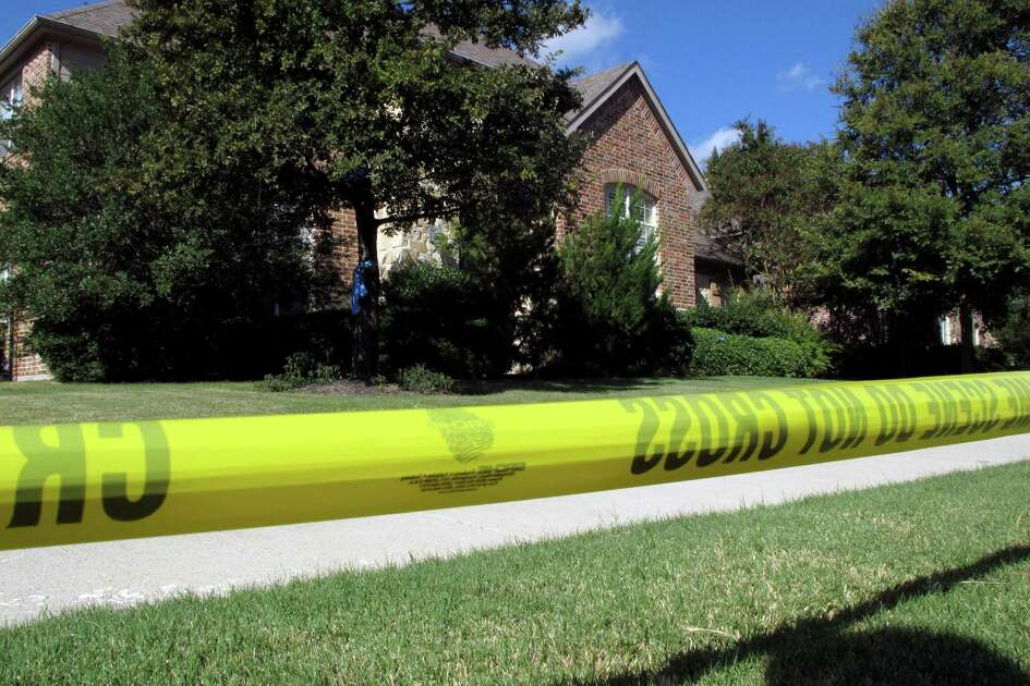 In this Thursday, Sept. 4, 2014 photo, police tape marks off the exterior of a Frisco, Texas, home were two bodies found Wednesday. The bodies of a man and a woman were found at the suburban Dallas home where a 10-year-old boy was found dead in January, whose mother,  Pallavi Dhawan was accused of killing him, police said. A medical examiner's report later said a natural cause was the most likely cause of the Jan. 29 death of the boy, Arnav Dhawan. (AP Photo/Nomaan Merchant)
