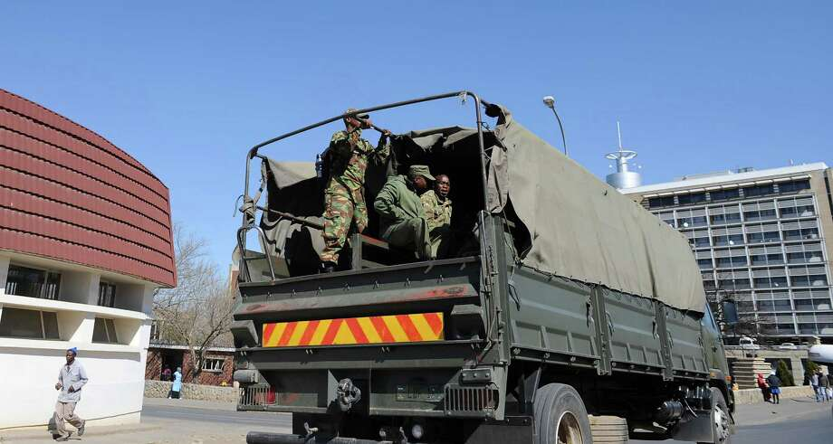 Soldiers atop a military vehicle are driven through the capital Lesotho Tuesday. Sept 2, 2014. Police have been told to abandon their posts and not wear uniforms to avoid being targeted in attacks in the kingdom's continuing power vacuum, an official said Tuesday. At least one policeman was killed when the military disarmed police stations on Saturday. Radios were also jammed in what the prime minister said was a clear coup attempt in the country of about 2 million people. (AP Photo) Photo: STR / AP