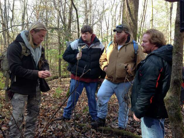 "Nick Lansing, second from left, observes survival expert, Creek Stewart, far left, with two other participants in the Weather Channel's new reality TV show, ""Fat Guys in the Woods."" (Photo courtesy the Weather Channel)"