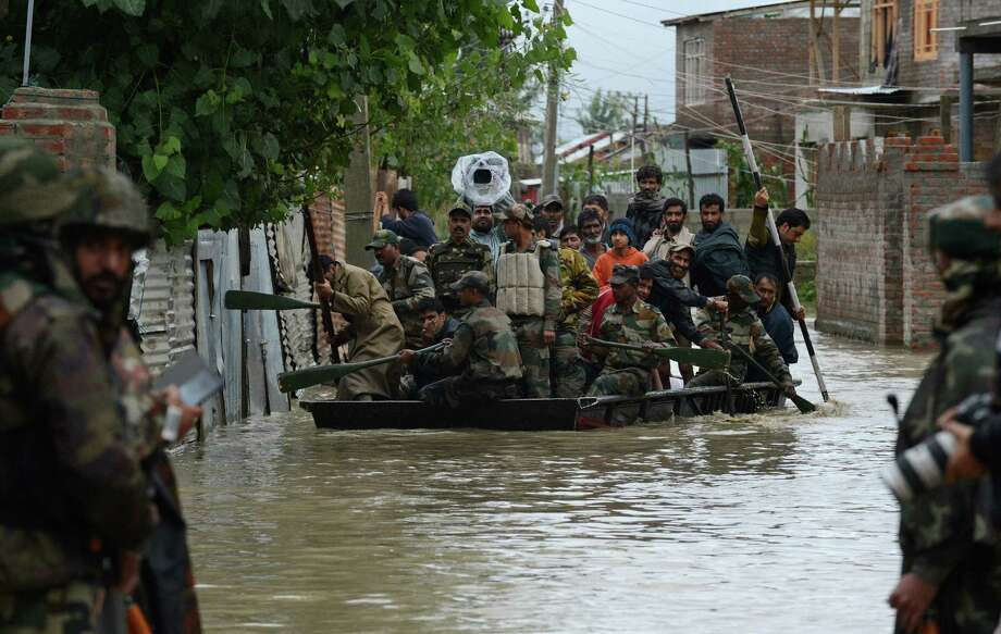 Indian soldiers paddle a raft as they assist Kashmiri residents during flood rescue operations in the outskirts of Srinagar. Hundreds of villages have been flooded. Photo: Tauseef Mustafa / Getty Images / AFP