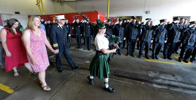 """Piper Michele Lyons leads Deputy Chief Francis """"Skip"""" Nerney, holding hands with wife Loretta as he passes members of the Albany Fire Department Friday afternoon Sept. 5, 2014 on the day of his retirement after 27 years in the fire service in Albany, N.Y.      (Skip Dickstein/Times Union) Photo: SKIP DICKSTEIN / 00028488A"""