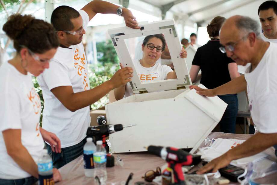 Lyanne Yurco, from left, Enrique Perez, Cindy Castillo and Frank Martinez install a door Friday as part of the building process of a miniature library sponsored by the United Way of Greater Houston. Low-income children's literacy is the goal. Photo: Marie D. De Jesus, Staff / © 2014 Houston Chronicle
