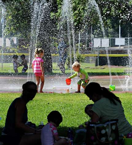 Families picnic in the shade as children keep cool in the West Side Rec park spray pool Friday Sept. 5, 2014, in Saratoga Springs.  (John Carl D'Annibale / Times Union) Photo: John Carl D'Annibale
