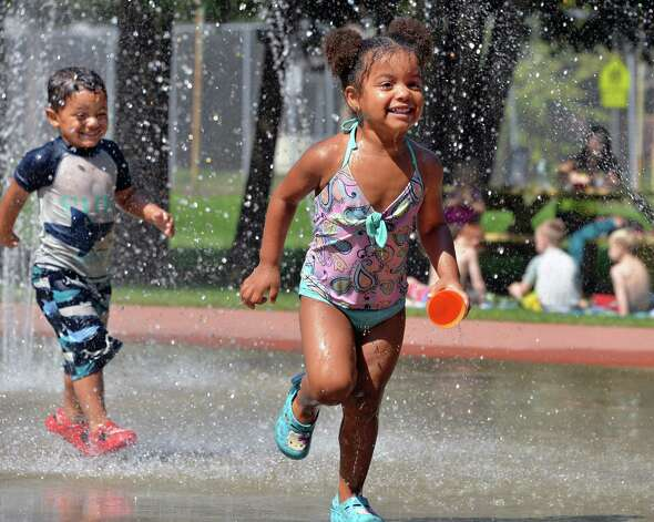 Three-year-old twins Jace, left, and Neveyah Langlois of Mechanicville keep cool in the West Side Rec park spray pool Friday Sept. 5, 2014, in Saratoga Springs.  (John Carl D'Annibale / Times Union) Photo: John Carl D'Annibale