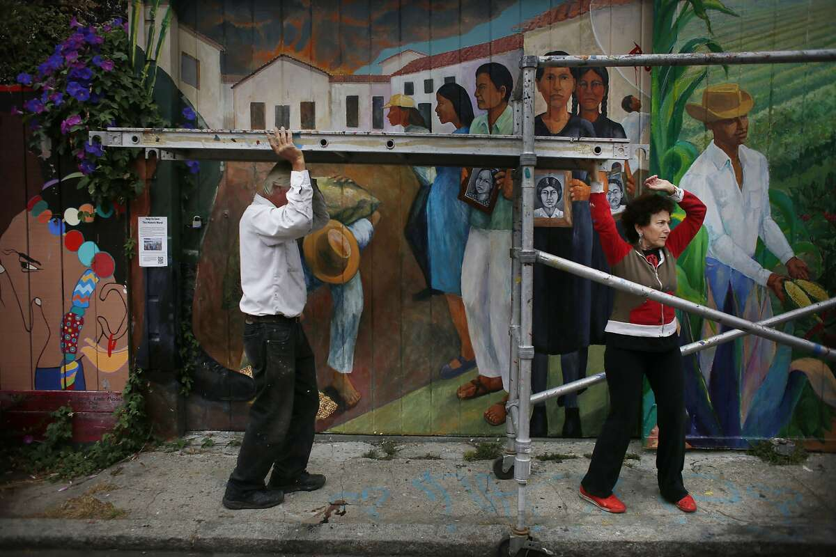 """O'Brien Thiele (l to r) and Miranda Bergman assemble scaffolding while restoring the mural """"Culture Contains the Seed of Resistance that Blossoms into the Flower of Liberation"""", which they originally painted 30 years ago on Balmy Alley on Friday, August 29, 2014 in San Francisco, Calif. It is the last complete PLACA mural on Balmy Alley."""