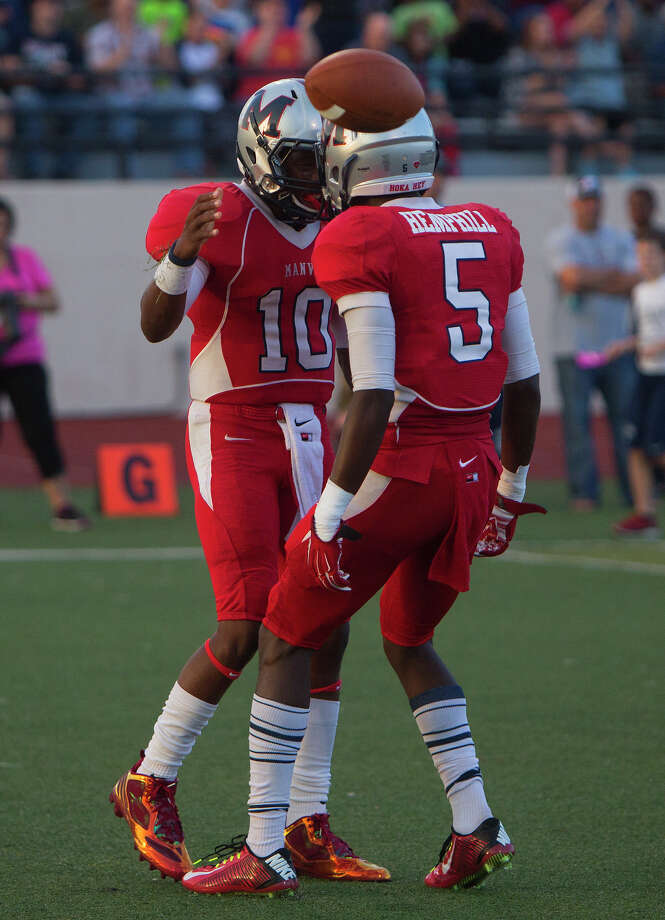 Manvel High School quarterback Deriq King, left, celebrates with Reggie Hemphill-Mapps after Kiong scored a touchdown during the first half of a football game against North Shore High School at Memorial Stadium, Friday, Sept. 5, 2014, in Alvin. Photo: Cody Duty, Houston Chronicle / © 2014 Houston Chronicle