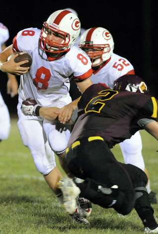 Guilderland's quarterback Andrew Sentz, left, diverts a tackle from Colonie's Chris Flood during their football game on Friday, Sept. 5, 2014, at Colonie High in Colonie, N.Y. (Cindy Schultz / Times Union) Photo: Cindy Schultz / 00028437A
