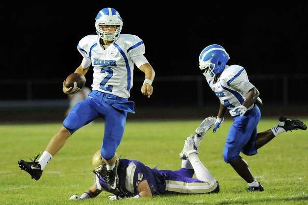 Shaker's quarterback Matt Woods, left, skips away from CBA's Patrick Pastore during their football game on Friday, Sept. 5, 2014, at Christian Brothers Academy in Colonie, N.Y. (Cindy Schultz / Times Union) Photo: Cindy Schultz / 00028436A