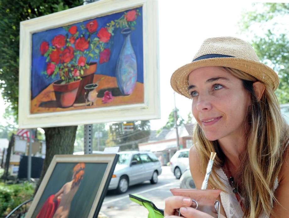 """Matilde Crosetti of Riverside holds a mate (a traditional South American caffeine-rich infused drink)  by one of her paintings that is titled the same, """"Mate,"""" during the 63rd annual Art Society of Old Greenwich Sidewalk Art Show and Sale on Sound Beach Avenue in Old Greenwich, Conn., Saturday morning, Sept. 6, 2014. Crosetti said she is a native of Argentina. Photo: Bob Luckey / Greenwich Time"""