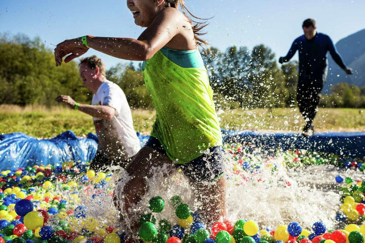 Participants dive into a Skittle ball pit during a 3.5 mile course - complete with 11 other obstacles such as mud pits - at the Beast Mode Challenge Saturday, September 6, 2014, Meadowbrook Farm in North Bend, Wash. Inspired by Seattle Seahawk Marshawn Lynch, the event benefitted the athlete's