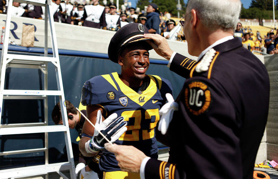 Cal band director Robert Calonico takes back his hat from defensive back Trey Cheek, who borrowed it to lead the fight song after Saturday's 55-14 win over Sacramento State. Photo: Scott Strazzante, Staff Photographer / The Chronicle / ONLINE_YES