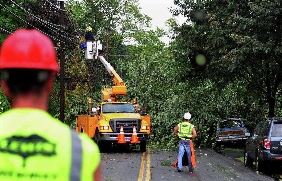 Emergency crews work on restoring power and removing a fallen tree after a severe storm swept through the neighborhood on Wakeman Road in Fairfield, Conn. on Saturday September 6, 2014. A driver passing by was caught in the fallen tree and had to be rescued by emergency personel. Photo: Christian Abraham / Connecticut Post