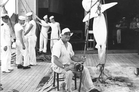 President Franklin Delano Roosevelt, in the well deck of USS Houston, with a shark he caught in Sullivan Bay, Galapagos Islands, in July 1938.