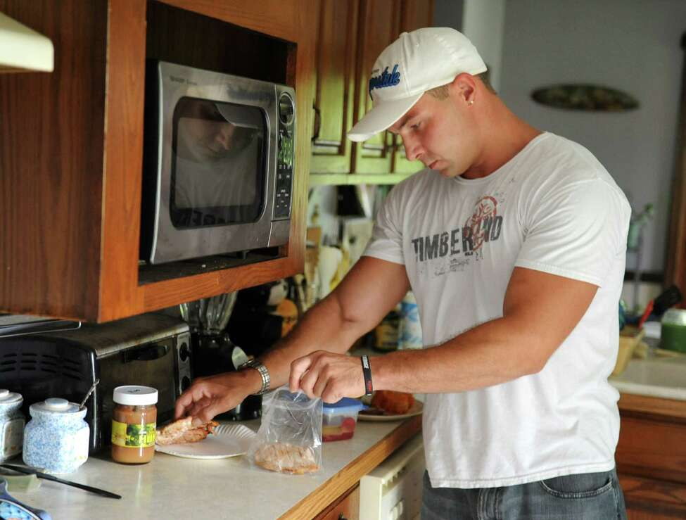 Emmanuel Donato, a recovering heroin addict and dealer, bags up extra chicken breast for later at his home on Tuesday, Aug. 12, 2014 in Altamont, N.Y. (Lori Van Buren / Times Union)