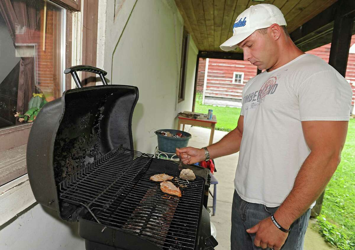 Emmanuel Donato, a recovering heroin addict and dealer, prepares a cooks some chicken breast on a grill at his home on Tuesday, Aug. 12, 2014 in Altamont, N.Y. (Lori Van Buren / Times Union)