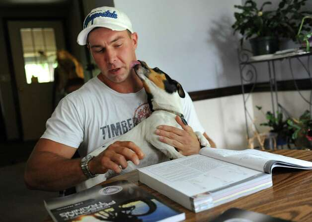 Emmanuel Donato, a recovering heroin addict and dealer, tries to study to be a personal trainer with a little distraction from his dog Pistol at his home on Tuesday, Aug. 12, 2014 in Altamont, N.Y.  (Lori Van Buren / Times Union) Photo: Lori Van Buren / 00028106A