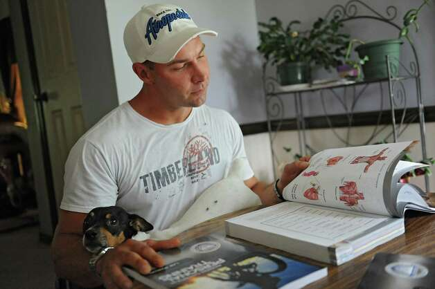 Emmanuel Donato, a recovering heroin addict and dealer, tries to study to be a personal trainer with his dog Pistol on his lap at his home on Tuesday, Aug. 12, 2014 in Altamont, N.Y.  (Lori Van Buren / Times Union) Photo: Lori Van Buren / 00028106A
