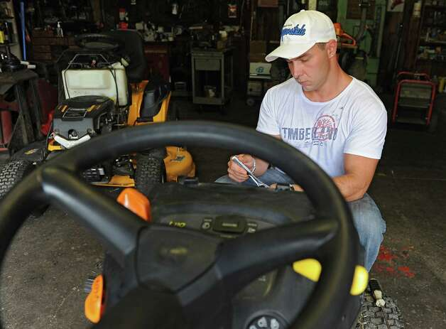 Emmanuel Donato, a recovering heroin addict and dealer, helps out his father by working on a tractor at his home on Tuesday, Aug. 12, 2014 in Altamont, N.Y.  (Lori Van Buren / Times Union) Photo: Lori Van Buren / 00028106A