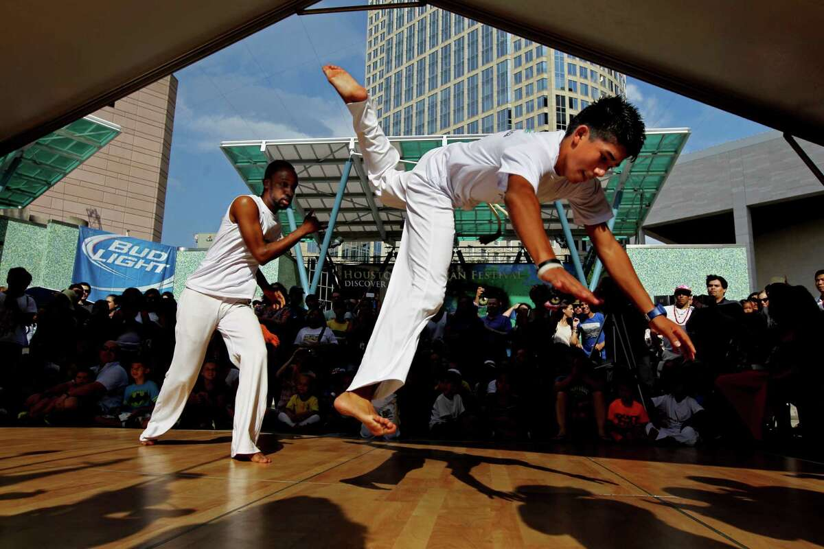 Idris Soyinka, of Houston, left, and Edwin Pineda, 14, of Houston, of Capoeira Luanda, perform for the crowd at the Houston Brazilian Festival, sponsored by the Brazilian Arts Foundation, at Jones Plaza Saturday, Sept. 6, 2014, in Houston, Texas. The event featured live music, performances, food and more.