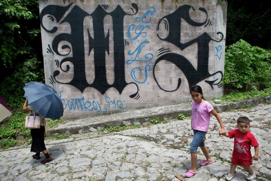 ADVANCE FOR SUNDAY, SEPT. 7 AND THEREAFTER - In this Thursday, Aug. 21, 2014 photo, a family walks by a wall covered by a symbol from the Mara Salvatrucha gang in Ilopango, El Salvador. In Ilopango and communities across El Salvador, the Mara Salvatrucha and their arch rivals, the 18th Street Gang, are de facto rulers. (AP Photo/Esteban Felix) Photo: Esteban Felix, STF / AP