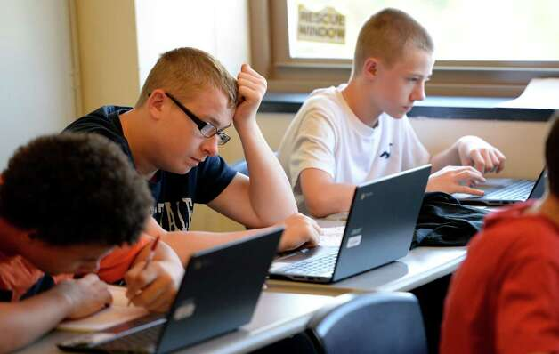 Mieguel Porter, left, Brendan Stanton, center and Grank VandeBogard members of the inaugural class of the Troy Riverfront  P-tech program work on their projects Thursday afternoon  Sept. 4, 2014, at Troy High School in Troy, N.Y.   (Skip Dickstein/Times Union) Photo: SKIP DICKSTEIN / 00028477A