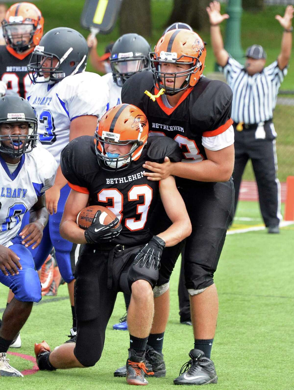Bethlehem's #33 Ben Tietjen, center, in congratulated by team mate #73 Hong Fe Huang after his touchdown during Saturday's game against Albany High Sept. 6, 2014, at Union College's Frank Bailey Field in Schenectady,NY. (John Carl D'Annibale / Times Union)