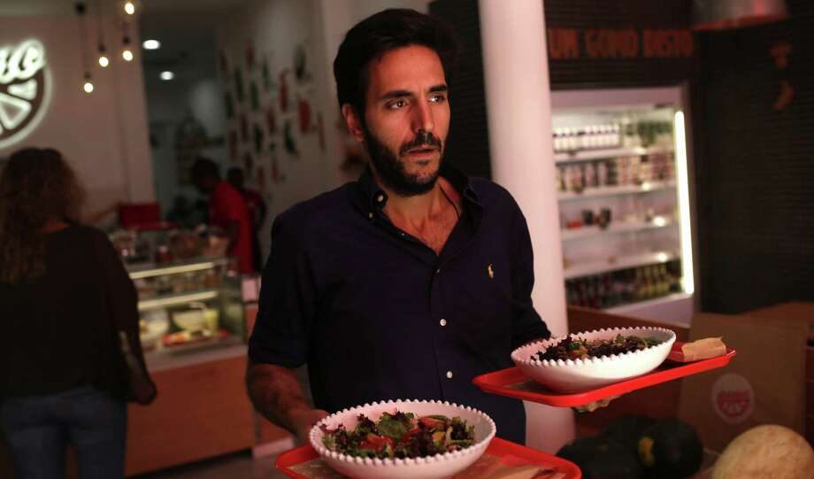 "Portuguese restaurant manager Jose Nunes Pereira carries food to customers who ""have to pay high taxes on their salaries and the 23 percent sales tax they have to pay at my restaurant."" Photo: Francisco Seco / Associated Press / AP"