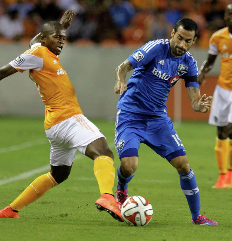 Houston Dynamo DaMarcus Beasley, left, and Montreal Impact Andres Romero battle for the ball during the first half of game at BBV Compass Stadium Saturday, Sept. 6, 2014, in Houston. Photo: Melissa Phillip, Houston Chronicle / © 2014  Houston Chronicle