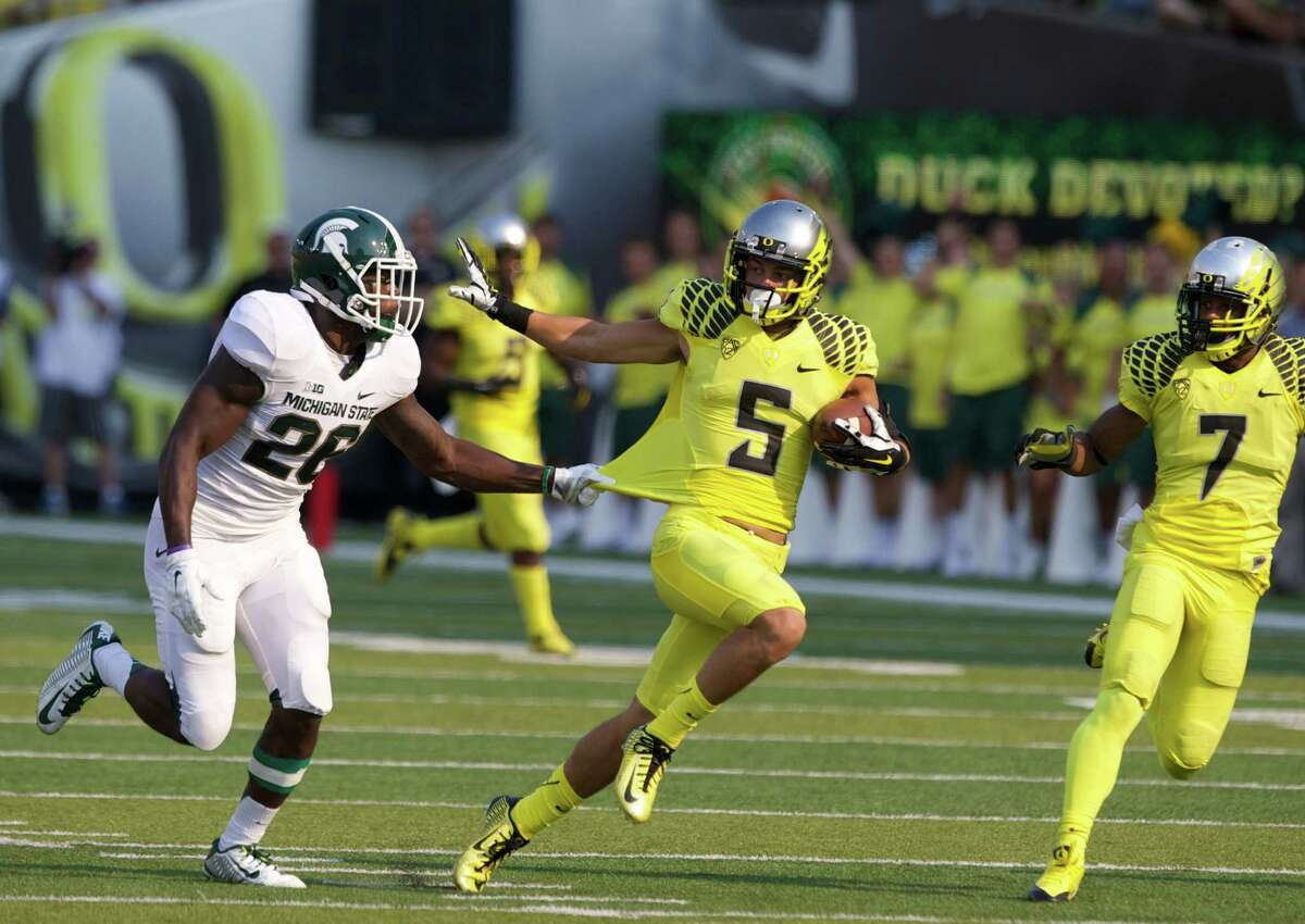 Oregon Ducks Devon Allen eludes tackle on his way to a second quarter touchdown against the Michigan State Spartans at Autzen Stadium, in Eugene, Oregon, Sat, Sept. 6, 2014. (AP Photo/The Oregonian, Thomas Booyd) MAGS OUT; TV OUT; LOCAL TELEVISION OUT; LOCAL INTERNET OUT; THE MERCURY OUT; WILLAMETTE WEEK OUT; PAMPLIN MEDIA GROUP OUT