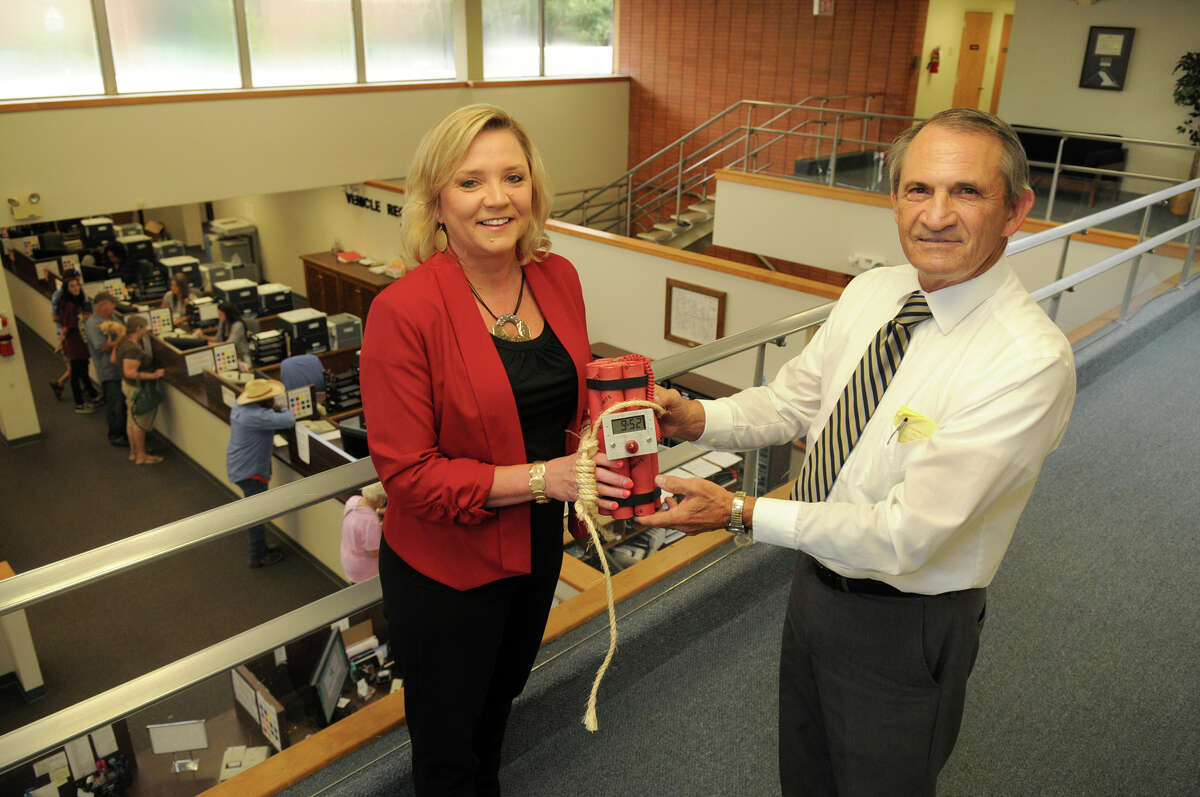 """J.R. Moore will be retiring as Montgomery County tax assessor-collector, symbolically handing over the job's responsibilities to chief deputy Tammy McRae, left, along with the novelty """"dynamite"""" clock he was given when he took over the office almost 28 years ago."""