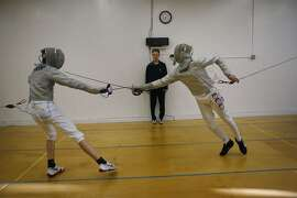 Robin Jeffry, 15, (left) tries to dodge a lung by Ethan Mullennix, 14, at Halberstadt Fencers' Club in San Francisco, Calif.