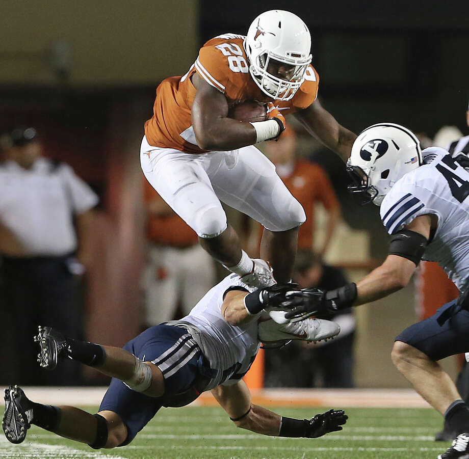 Texas' Malcolm Brown takes to the air to try to find room to maneuver against a stubborn BYU defense. Photo: TOM REEL