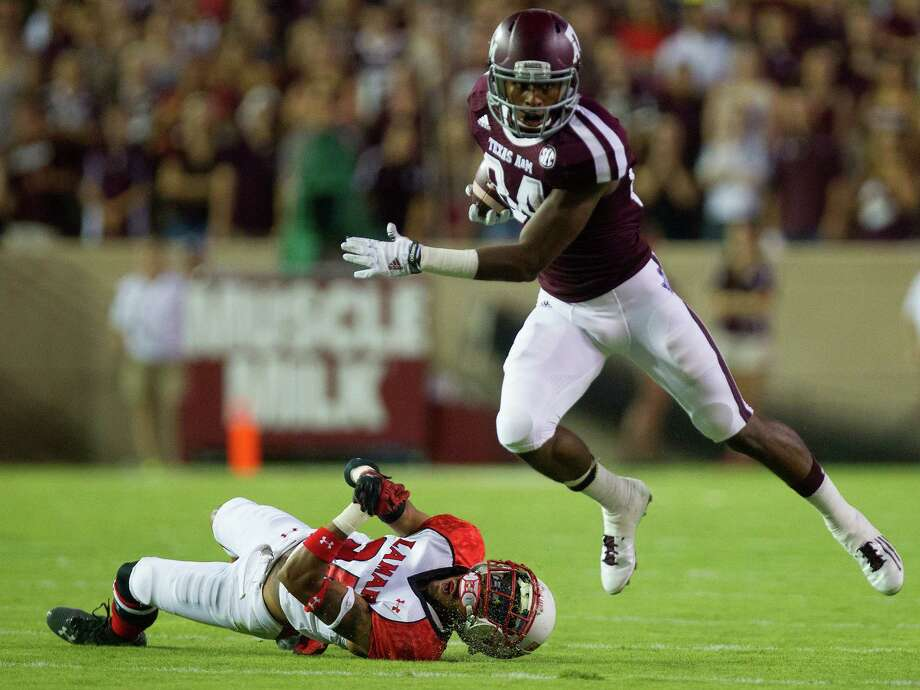 Texas A&M Aggies wide receiver Malcome Kennedy shakes a tackle from Lamar Cardinals defensive back DaQuan Stewart during the first half on an NCAA college football game at Kyle Field, Saturday, Sept. 6, 2014, in College Station. Photo: Cody Duty, Houston Chronicle / © 2014 Houston Chronicle