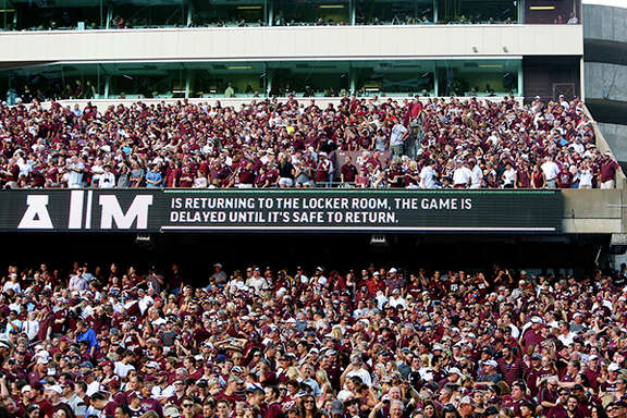 Texas A&M Aggie fans wait while the game against the Lamar Cardinals is delayed at Kyle Field, Saturday, Sept. 6, 2014, in College Station. The delay came just before kick-off.