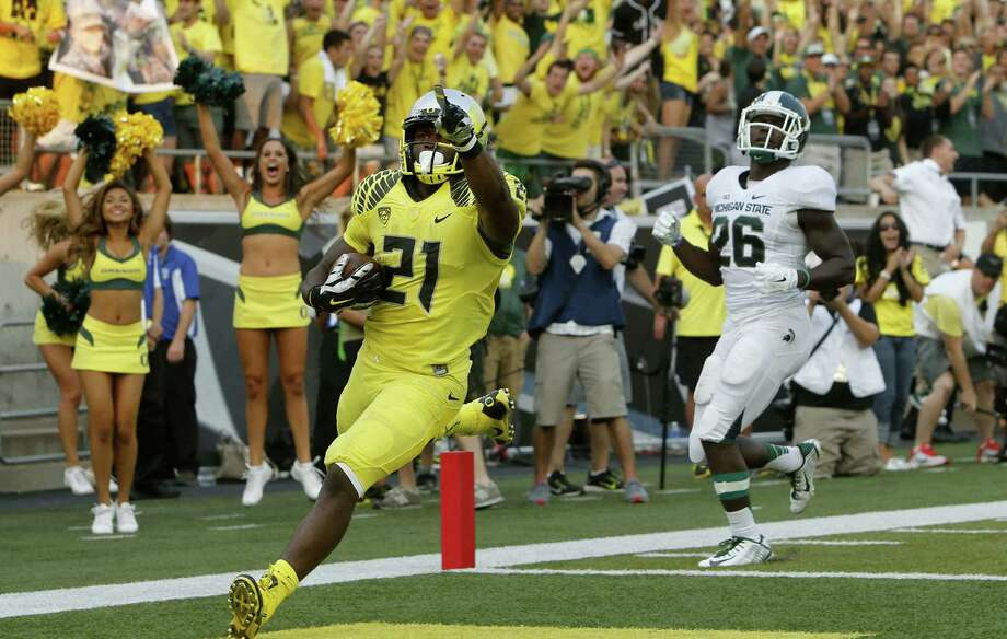 Oregon's Royce Freeman acknowledges the Autzen Stadium faithful after outrunning Michigan State's R.J. Williamson to score a fourth-quarter touchdown Saturday afternoon. Photo: Chris Pietsch / Associated Press / FR24134 AP