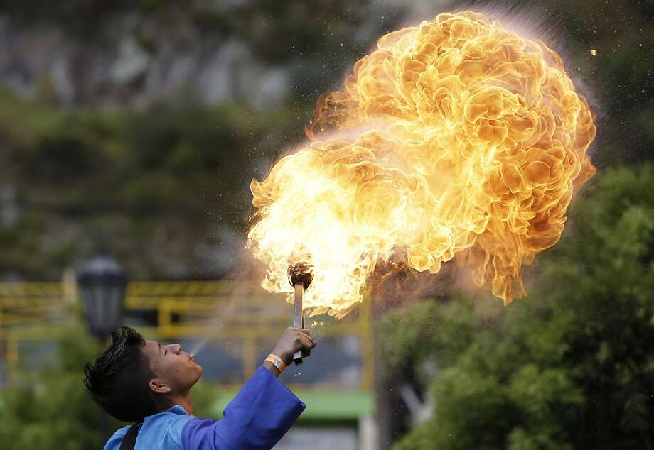 A young fire breather marches in a parade as part of the XXII National Andina Dance Competition's opening ceremony in Nemocon, Colombia, Saturday, Sept. 6, 2014. Forty dance groups from different parts of Colombia arrived in Nemocon, just north of Bogota, to take part in the two-day national dance competition. (AP Photo/Fernando Vergara) Photo: Fernando Vergara, Associated Press
