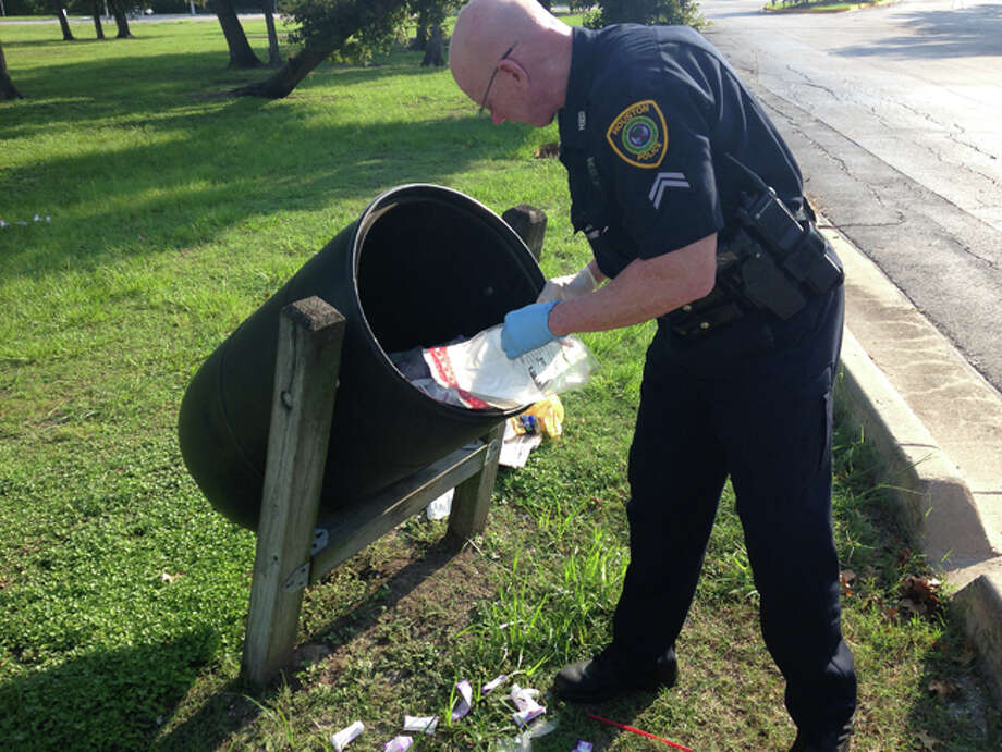 A Houston police officer investigates dozens of armored car bags found in a trash bin Sunday morning near the picnic area in MacGregor Park. Photo: Dane Schiller / Houston Chronicle