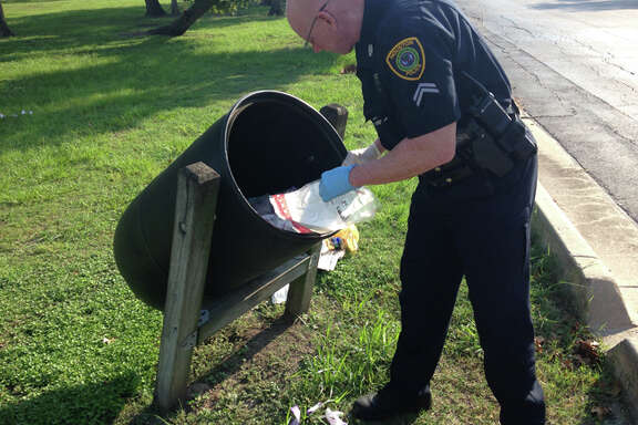 A Houston police officer investigates dozens of armored car bags found in a trash bin Sunday morning near the picnic area in MacGregor Park.