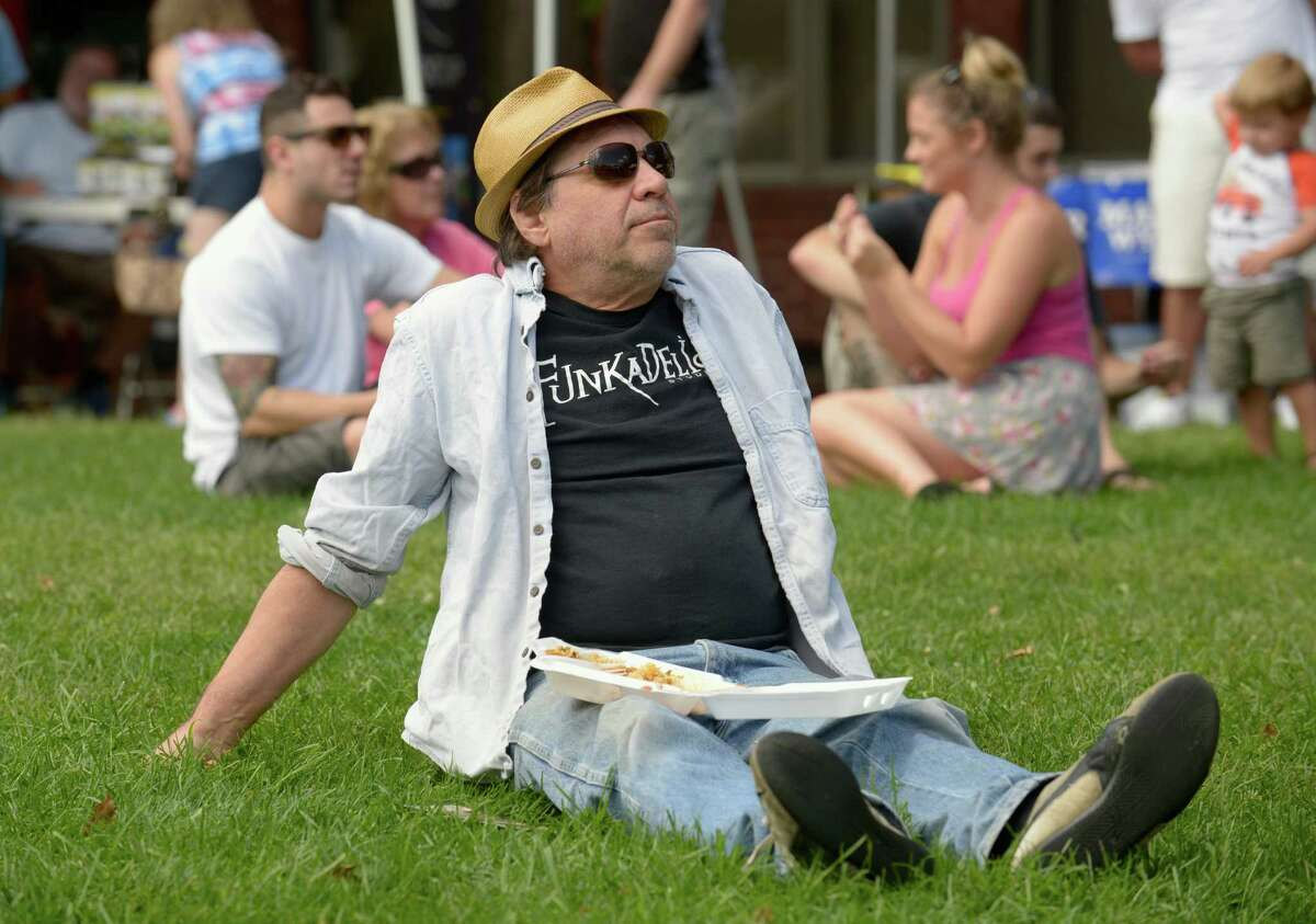 Russ Preston, 66, of Danbury, relaxes on the CityCenter Green and enjoys some food and music during the Taste of Greater Danbury, on Sunday, September 7, 2014, in Danbury, Conn.